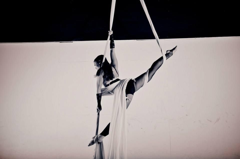 woman hanging from silk posing for black and white photoshoot doing extreme split, aerial silk classes, aerial silks