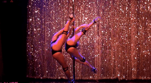 video image of two women performing doubles routine on stage wearing runners themed magic mike