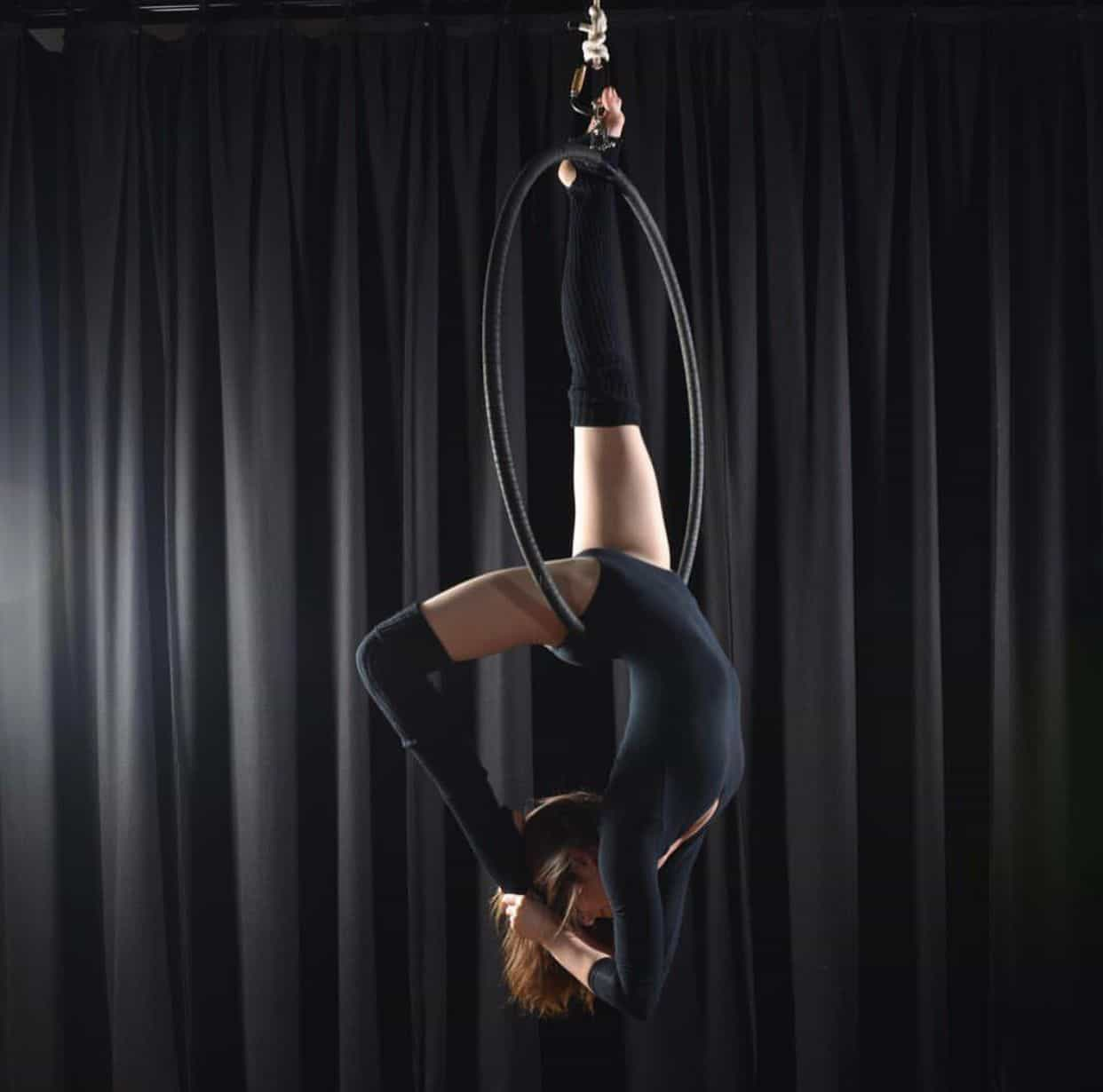 woman training aerial hoop for photoshoot wearing black doing flexy back trick, aerial silk classes
