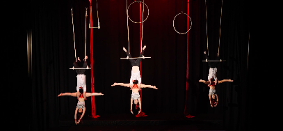 video image of circus routine on stage with 6 people doing doubles trapeze, aerial fitness, aerial silk classes