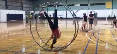 video image of woman training German wheel at a gym, aerial fitness, aerial silks, aerial silk classes, aerial classes