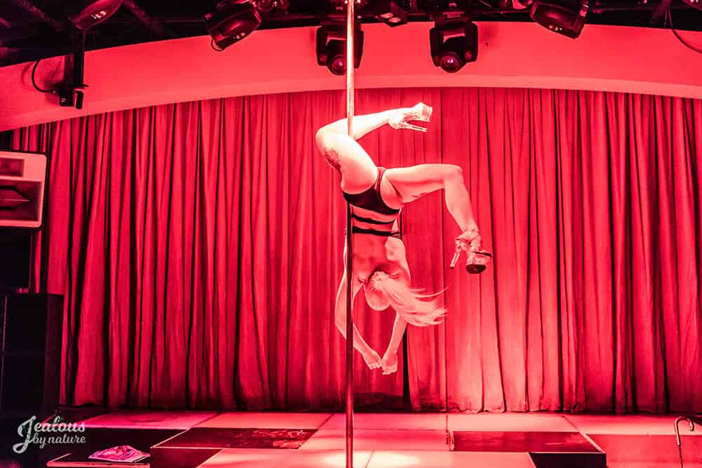 Woman performing in pole competition red colour lights upside down trick, pole fitness, pole dancing